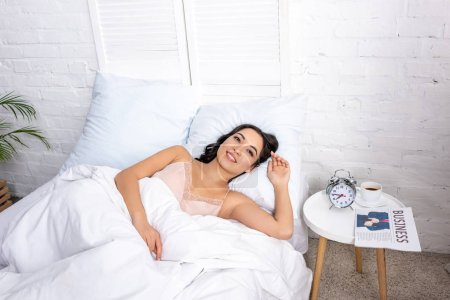 Photo for Beautiful smiling woman laying in bed near bedside table with newspaper and cup of coffee - Royalty Free Image