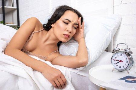 Photo pour Jolie jeune femme couchée au lit et regardant réveil montrant quart à huit heures du matin - image libre de droit