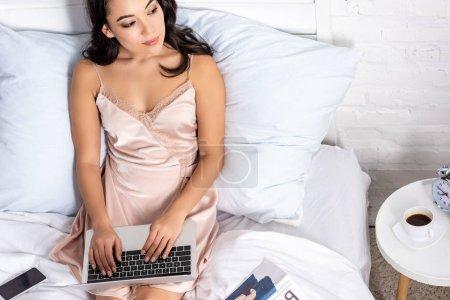 Photo pour Jeune asiatique freelance en élégant hightie utilisant l'ordinateur portable tout en restant dans son lit et regardant la fenêtre - image libre de droit