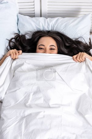 Photo for Young beautiful asian woman laughing while looking out of blanket - Royalty Free Image