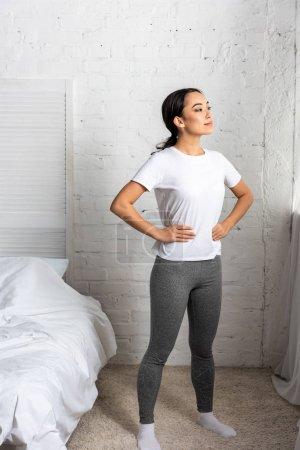 Photo pour Jeune femme asiatique dans des leggings t-shirt et gris blancs debout dans la chambre tenue mains aux hanches - image libre de droit