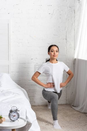 Photo for Asian woman in white t-shirt and grey leggings doing lunges exercises - Royalty Free Image