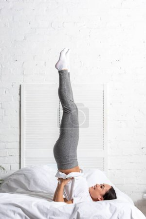 Photo for Asian woman in white t-shirt and grey leggings doing shoulder stand pose exercise in bed - Royalty Free Image
