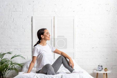 Photo pour Femme asiatique dans des leggings t-shirt et gris blancs assis dans son lit et se reposer après l'exercice du matin - image libre de droit