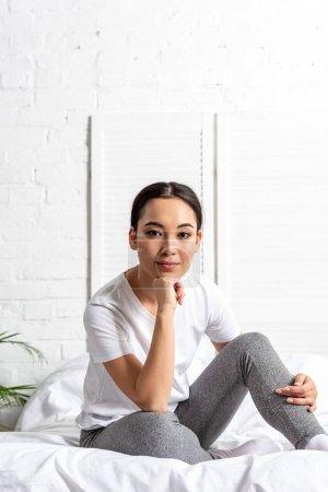 Photo pour Jeune femme asiatique assise dans son lit matin - image libre de droit