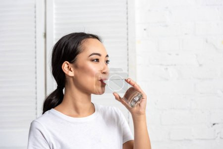 Photo for Beautiful young asian woman drinking water in morning - Royalty Free Image
