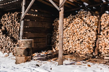 pile of firewood in wooden building at sunny day in winter