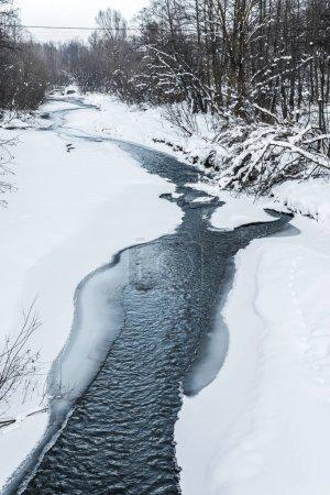 Photo pour Ruisseau froid de montagne dans la forêt enneigée dans les carpates - image libre de droit