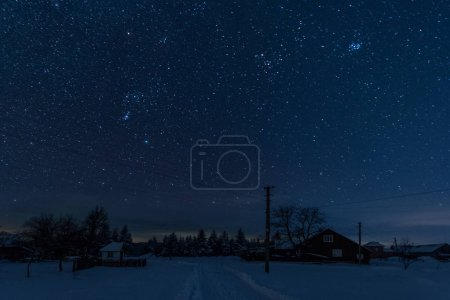 Photo for Starry night sky above village covered with snow in carpathian mountains - Royalty Free Image