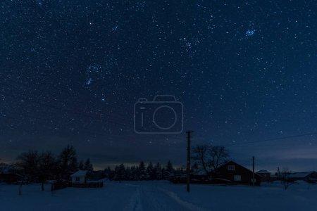 Photo pour Ciel étoilé au-dessus de village recouvert de neige dans les montagnes des Carpates - image libre de droit