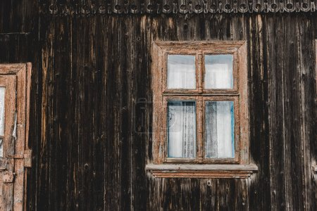 Photo for Weathered aged brown wooden house with window - Royalty Free Image