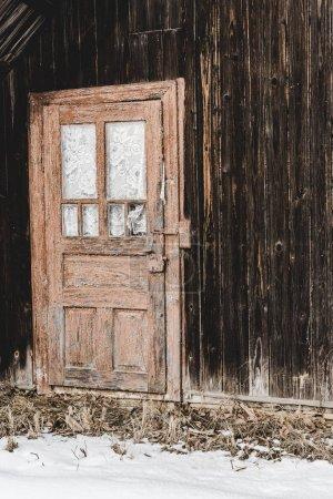 Foto de Antigua casa de madera desgastada con la puerta en invierno - Imagen libre de derechos