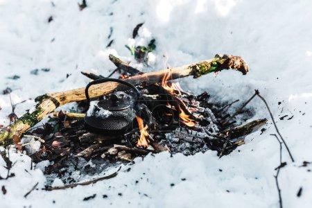 Foto de Hervidor de agua hirviendo con vapor en hoguera en el bosque de invierno - Imagen libre de derechos