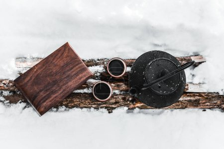 top view of kettle, cups with tea and wooden box on logs among snow