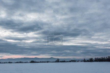 Photo pour Paysage de montagnes carpates couvertes de neige avec ciel nuageux et arbres à l'aube - image libre de droit
