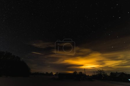 Photo for Starry dark sky and yellow light in carpathian mountains at night in winter - Royalty Free Image