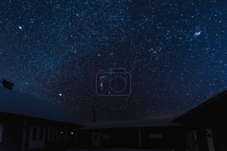 Photo for Starry dark sky and houses covered with snow at night in winter - Royalty Free Image