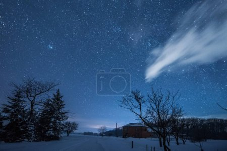 Photo for Starry dark sky and house in carpathian mountains at night in winter - Royalty Free Image