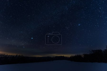 starry dark sky in carpathian mountains at night in winter