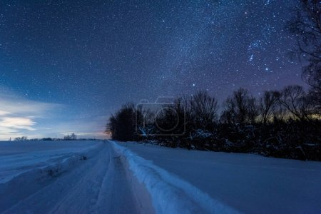 Photo for Starry dark sky and snowy road in carpathian mountains at night in winter - Royalty Free Image