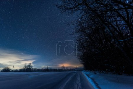 Photo for Starry dark sky and road in carpathian mountains at night in winter - Royalty Free Image
