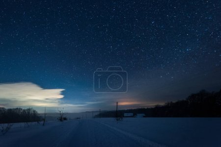 starry dark sky and road in carpathian mountains at night in winter