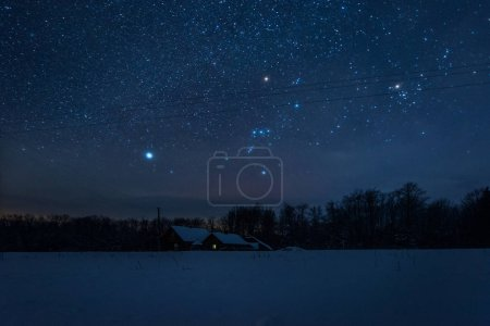 starry dark sky and house in carpathian mountains at night in winter