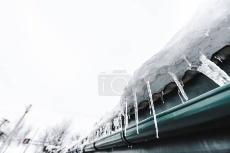 Photo for Selective focus of sharp icicles on roof against clear sky - Royalty Free Image