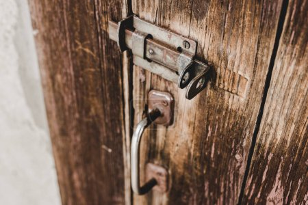 Photo for Close up of wooden weathered door with rusty handle and lock - Royalty Free Image