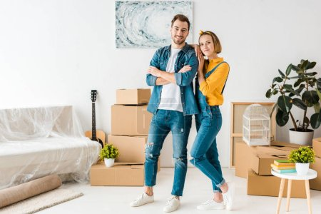 Photo for Full length view of happy couple standing near cardboard boxes at home - Royalty Free Image