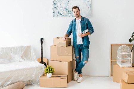 Foto de Vista de longitud completa del hombre sonriente en jeans de pie cerca de cajas de cartón en el nuevo hogar - Imagen libre de derechos