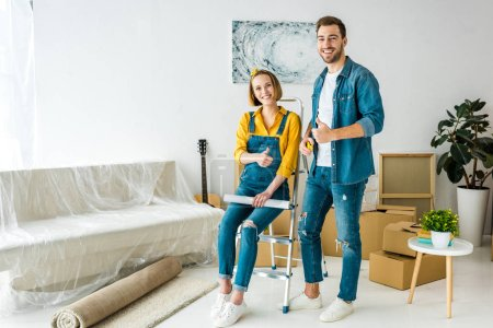 Photo for Full length view of couple with cardboard boxes and blueprint showing thumbs up - Royalty Free Image