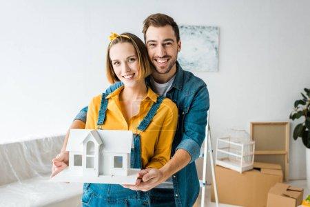 Photo pour Maison de jouet de couples de sourire et regardant l'appareil-photo à la maison - image libre de droit