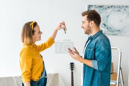 Photo pour Vue de côté de femme de sourire dans la chemise jaune affichant des clefs au mari - image libre de droit