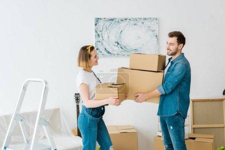 Photo pour Couples joyeux dans des jeans retenant des boîtes en carton et regardant l'un l'autre à la maison - image libre de droit
