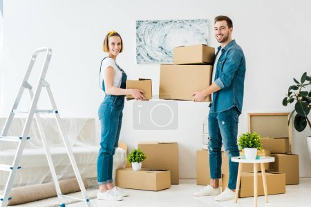 Photo for Full length view of smiling couple holding cardboard boxes and looking at camera - Royalty Free Image