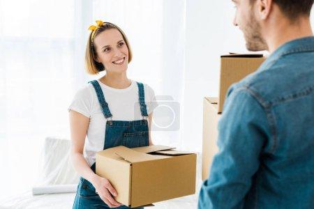 Photo pour Couple joyeux tenant des boîtes en carton et se regardant - image libre de droit