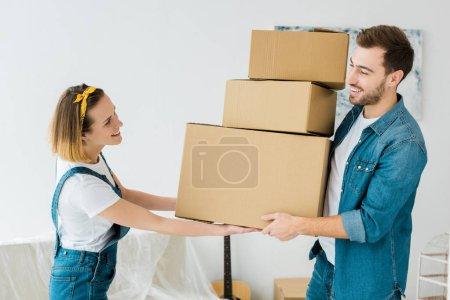 Photo pour Couples heureux retenant des boîtes en carton et regardant l'un l'autre - image libre de droit