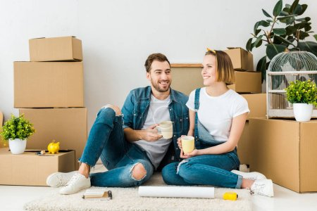 Photo for Joyful couple drinking coffee while sitting on floor near cardboard boxes - Royalty Free Image