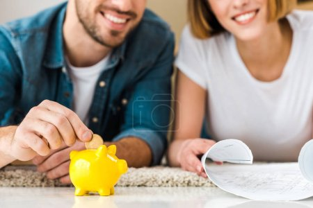 cropped view of smiling couple with blueprint and piggy bank lying on carpet