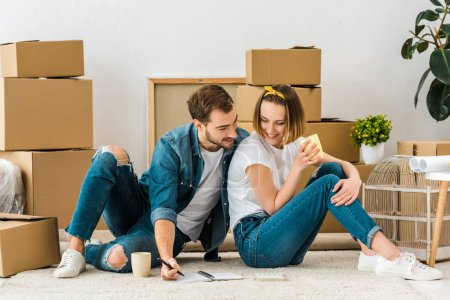Photo for Smiling couple with notebook sitting on carpet near cardboard boxes and drinking coffee - Royalty Free Image