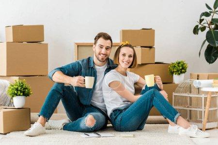 Photo pour Café joyeux de couples buvant tout en s'asseyant sur l'étage près des boîtes en carton - image libre de droit