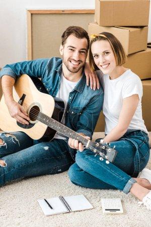 Photo pour Homme souriant assis sur le tapis avec sa femme et jouant de la guitare acoustique - image libre de droit