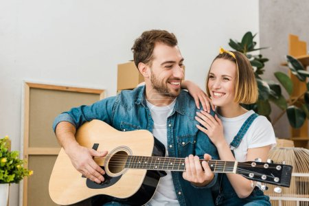 Photo for Smiling man playing acoustic guitar to wife at home - Royalty Free Image
