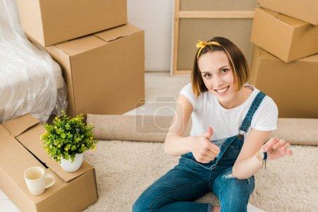 Photo pour Vue d'angle élevé de la femme retenant des clefs et affichant le pouce vers le haut près des boîtes en carton - image libre de droit