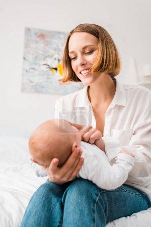 Photo pour Mère heureuse en chemise blanche tenant bébé à la maison - image libre de droit