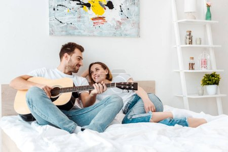 Smiling man lying on bed with wife and playing guitar