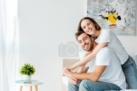 Photo for Smiling couple in white t-shirts embracing on bed in bedroom - Royalty Free Image