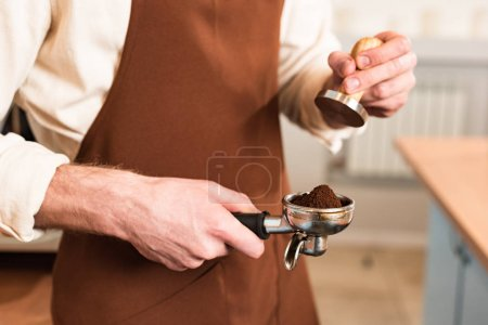 Photo for Cropped view of barista in brown apron holding portafilter with ground coffee and tamper - Royalty Free Image