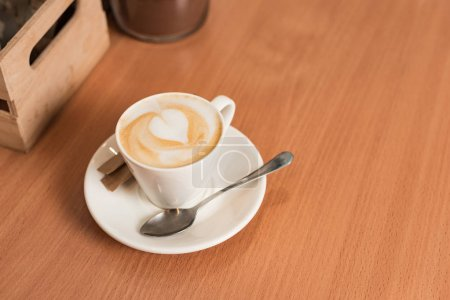 Photo for Cup of coffee with saucer and spoon on wooden table - Royalty Free Image